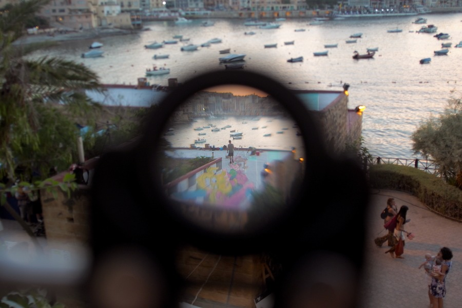 Looking through an optic on a tripod placed by the roof artists through it