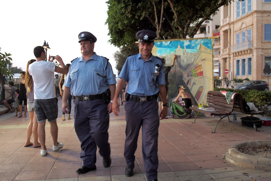 A police officer smiling after looking back at the the live painting