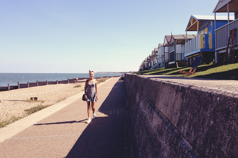Charlotte walking by Beach Huts